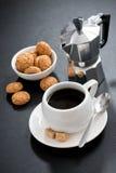Kopp kaffe- och italienarekakabiscotti på svart bakgrund Royaltyfri Fotografi