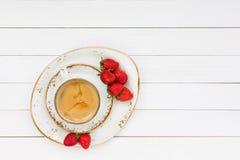 Kopp kaffe och jordgubbar på den vita trätabellen Top beskådar Arkivfoto