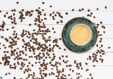 Kopp kaffe- och kaffebönor på den vita trätabellen Top beskådar Arkivfoto