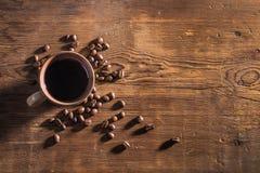 Kopp kaffe- och kaffebönor på tabellen Arkivfoto