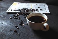Kopp kaffe- och kaffebönor på tidningspapper på svart backg royaltyfri fotografi