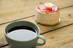 Kopp kaffe och kaka p? tr?tabellen fotografering för bildbyråer