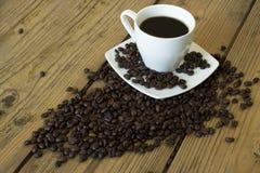 Kopp kaffe och kaka p? tr?tabellen arkivbild