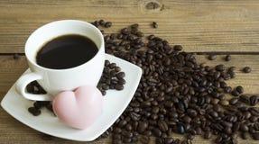 Kopp kaffe och kaka p? tr?tabellen royaltyfri foto