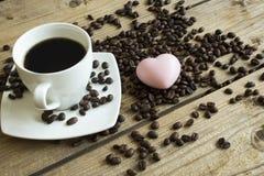 Kopp kaffe och kaka p? tr?tabellen arkivfoton