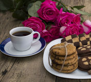 Kopp kaffe och kakor på en platta med en bukett av rosor Arkivfoto