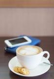 Kopp kaffe och kex på träbräde Arkivfoto
