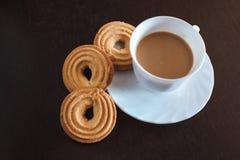 Kopp kaffe och kexar arkivbild