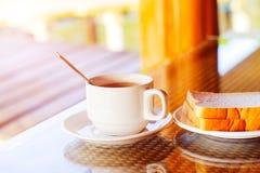 Kopp kaffe och maträtt av bröd på frukosttabellen i moen Royaltyfria Foton