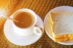 Kopp kaffe och maträtt av bröd på frukosttabellen i morgonen Fotografering för Bildbyråer