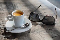 Kopp kaffe och par av exponeringsglas på tappningtabellen Mjuk fokus w royaltyfria foton