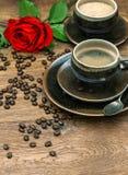Kopp kaffe och röd rosblomma festlig inställningstabell Arkivbilder
