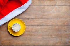 Kopp kaffe och Santa Claus hatt på det underbara bruna trä Arkivbild