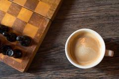 Kopp kaffe och schack-bräde vid närbild på en träbakgrund Sort från över royaltyfri fotografi