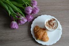 Kopp kaffe och smaskiga giffel med blommor Arkivbilder