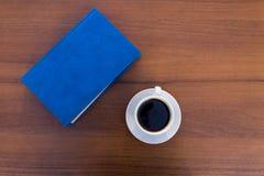 Kopp kaffe och stängd bok på trätabellen arkivfoto