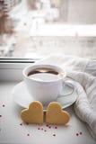 Kopp kaffe och två kakor i formen av en hjärta mot th Royaltyfri Foto