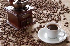 Kopp kaffe på bönor för ett bakgrundskaffe Royaltyfri Foto