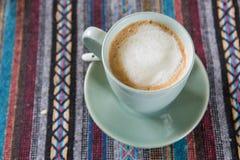 Kopp kaffe på bordduk Arkivfoto