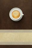 Kopp kaffe på brun bakgrund arkivbild
