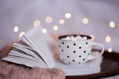 Kopp kaffe på den öppna boken Arkivfoto