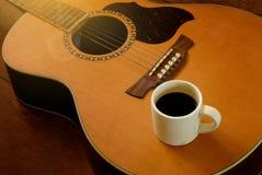 Kopp kaffe på den akustiska gitarren Royaltyfri Foto