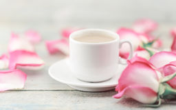 Kopp kaffe på den lantliga trätabellen i en ram av rosa rosor G royaltyfri fotografi