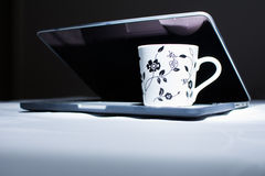 Kopp kaffe på en bärbar dator Mörk skärm Royaltyfri Fotografi