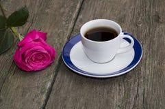 Kopp kaffe på en gammal tabell och närliggande en ros Royaltyfri Foto