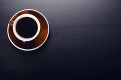 kopp kaffe på en mörk tabell Begrepp av affären Bärbar dator kaffe, klocka Arkivbild