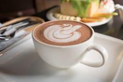 Kopp kaffe på en tabell i kafé med rostat bröd för suddighetskafébakgrund och suddighetshonung, tappningfillter Arkivbild