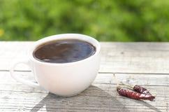 Kopp kaffe på en trätabell och chili Royaltyfri Foto