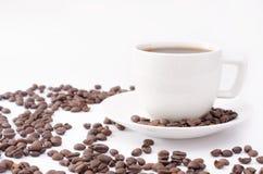 Kopp kaffe på en vit bakgrund med bönor arkivfoto