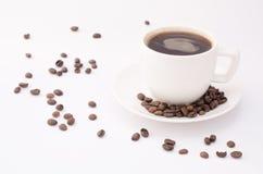 Kopp kaffe på en vit bakgrund med bönor royaltyfria bilder