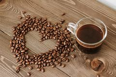 Kopp kaffe på ett magasin och kaffebönor i formen av en hjärta fotografering för bildbyråer