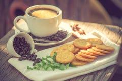 Kopp kaffe på ett träbräde och kex Arkivfoto