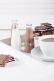 Kopp kaffe på ett vitt magasin med bruna kakor och choklad M Royaltyfri Foto