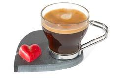 Kopp kaffe på fotboll för stenhjärtaform, med röd chokladhjärta Arkivbilder