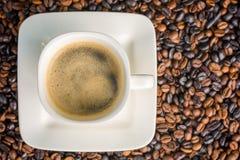 Kopp kaffe på grillade kaffebönor som fotograferas från över med kopieringsutrymme arkivfoto