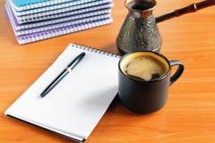 Kopp kaffe på kontorsskrivbordet med anteckningsboken royaltyfria bilder
