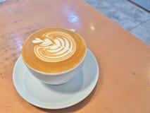 Kopp kaffe på tabellen med lattekonst Arkivfoto