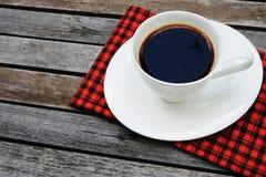 Kopp kaffe på träbakgrunds- och kopieringsutrymme med den röda näsduken arkivfoto