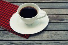 Kopp kaffe på träbakgrunds- och kopieringsutrymme med den röda näsduken arkivfoton