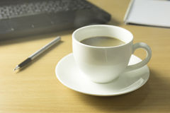 Kopp kaffe på träskrivbordet Arkivbilder