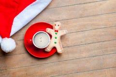 Kopp kaffe, pepparkakaman och Santa Claus hatt på under Arkivfoto