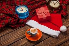 Kopp kaffe, Santa Claus, ringklockor och gåva på wonderfen Royaltyfri Foto