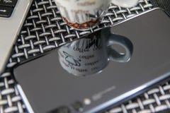 Kopp kaffe-, smartphone- och bärbar datoranteckningsbok på tabellen arkivbilder
