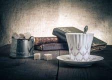 Kopp kaffe, sockerbunke och bunt av gamla böcker på det gamla trät Arkivfoto