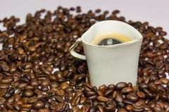 Kopp kaffe som en hjärta omgiven böna Arkivfoton