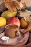 Kopp kaffe, stearinljus och frukter Arkivbild